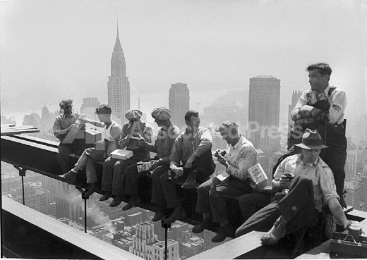 Construction Workers Take A Lunch Break On A Steel Beam
